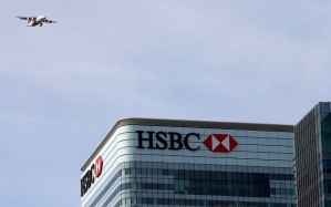 A plane flies past the HSBC building in Canary Wharf
