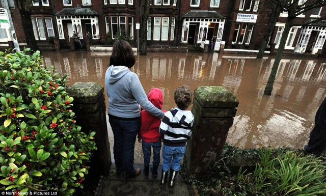 2F1B83CF00000578-3348001-A_woman_and_two_children_assess_the_severe_flooding_after_awakin-a-37_1449464031554.jpg